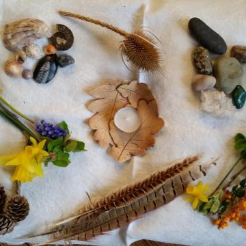 A table with a candle, flowers, shells and feathers