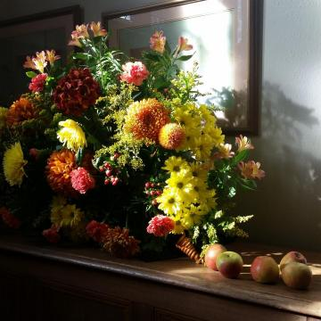 A flower arrangement with some apples beside it