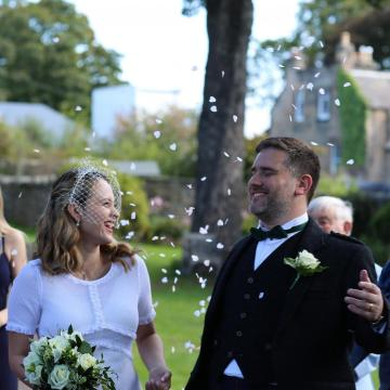 Couple in the garden being showered with confetti
