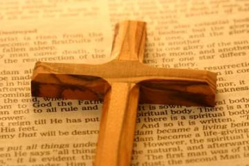 a wooden cross on an open bible