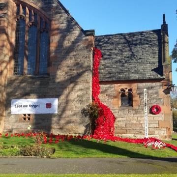 The church wall porch covered with a cascade of red knitted poppies and a banner: lest we forget