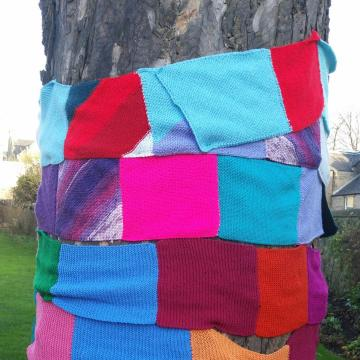 The trunk of a tree wrapped in a multicoloured knitted scarf